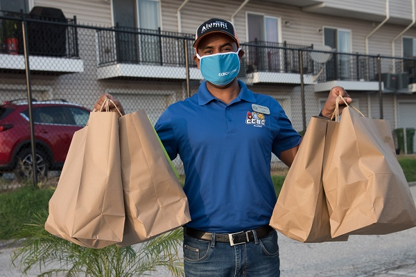 Kabish Shah holding four bags with mask on